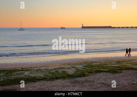 LES SABLES D'OLONNE, FRANCE: The beach at sunset with the jetty and the lighthouse in the background - Stock Photo