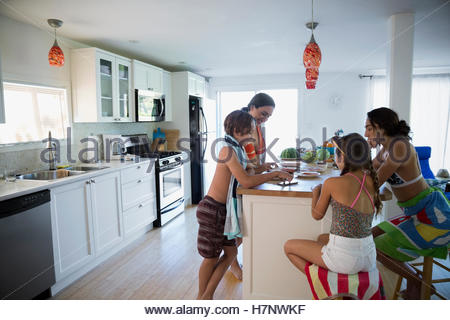 Family in bathing suits eating at kitchen island - Stock Photo