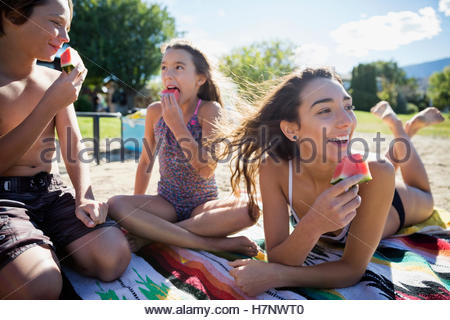 Brother and sisters eating watermelon on sunny summer beach - Stock Photo
