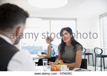 Smiling businesswoman and businessman eating lunch in office cafeteria - Stock Photo