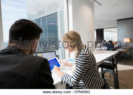 Business people using digital tablet at urban office window - Stock Photo
