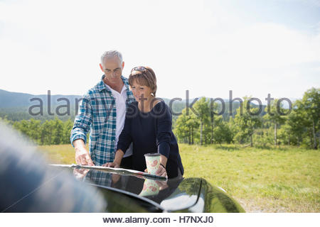 Mature couple looking at map on automobile hood at sunny rural overlook - Stock Photo
