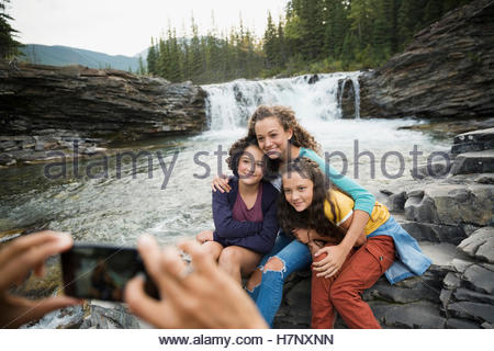 Sisters being photographed by mother at waterfall - Stock Photo