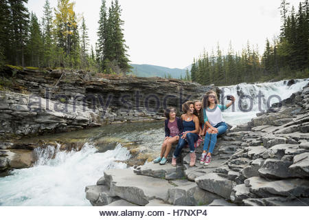 Mother and daughters taking selfie with camera phone at waterfall - Stock Photo