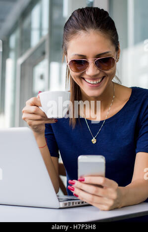Excited beautiful girl reading e-mail with good news in a smartphone in a coffee shop with a window in the background - Stock Photo