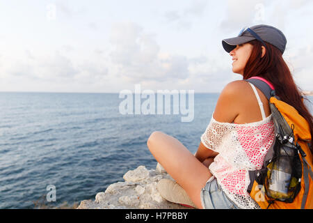 Smiling pretty young tourist admiring the picturesque sea view - Stock Photo