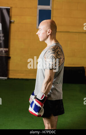 Boxer standing with boxing gloves in fitness studio - Stock Photo