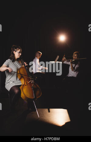 Three female students playing double bass, violin and piano - Stock Photo