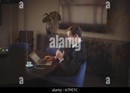Businessman using laptop while drinking water - Stock Photo