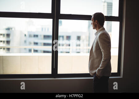 Thoughtful businessman looking through window - Stock Photo