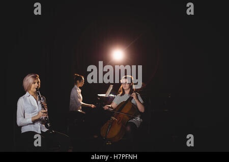Three female students playing double bass, clarinet and piano - Stock Photo