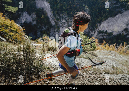 closeup young woman runner with walking poles running steep cliff during Crimea mountain marathon - Stock Photo