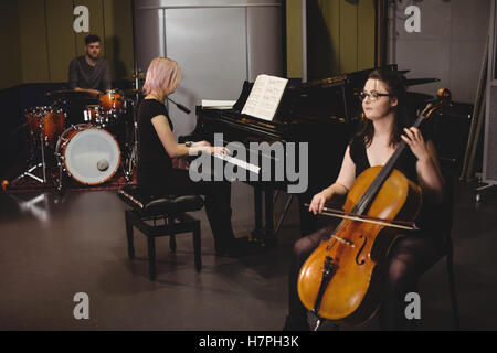 Group of students playing double bass, drum set and piano - Stock Photo