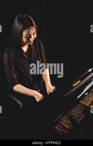 Female student playing piano - Stock Photo