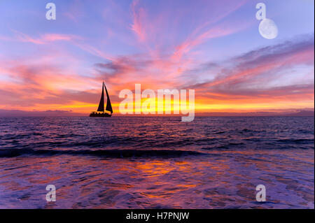 Sailboat ocean sunset is a silhouette of a sailboay sailing along the ocean water with a colorful vivid sunset sky - Stock Photo