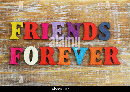 Friends forever written with colorful wooden letters on rustic surface - Stock Photo