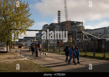 Workers of the New Safe Confinement passing the wrecked reactor no. 4 with its old enclosing sarcophagus. Chernobyl - Stock Photo