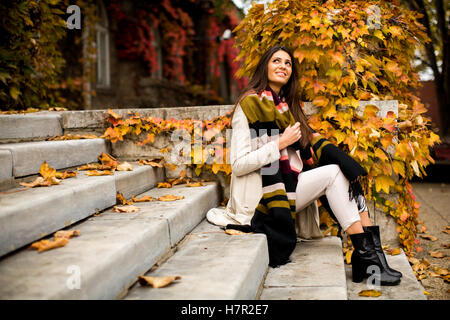 Young woman sitting on the steps outside in autumn day - Stock Photo