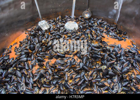 Mussels in red sauce in big cauldron on a Street market - Stock Photo