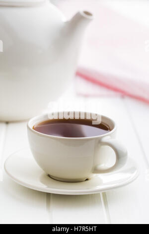 A cup of black tea and teapot on white table. - Stock Photo