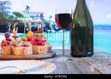 Set of Spanish tapas served on a sliced baguette with red wine on wooden table against the sea - Stock Photo