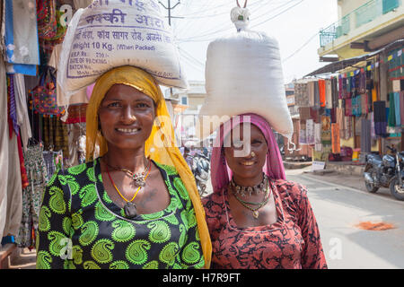 Two women carrying sacks of rice or flour on their heads in the traditional Indian manner, Pushkar, India - Stock Photo
