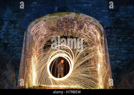 Spinning steel wool with a long exposure to create an interesting image - Stock Photo