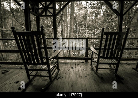 Empty Rocking Chairs On Front Porch. Two empty wooden rocking chairs on a wooden front porch overlooking the forest. - Stock Photo