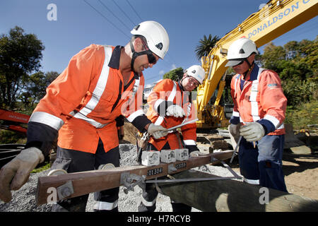three power company workers prepare a pole before replacing high voltage power cables blue sky - Stock Photo