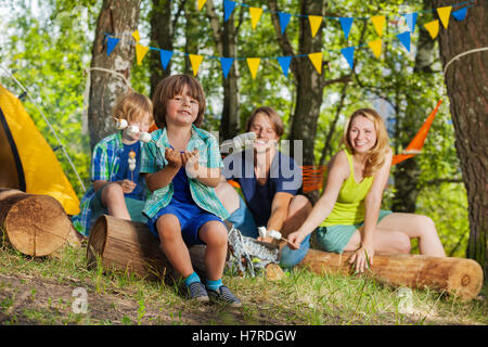 Happy little boy eating marshmallow at campsite - Stock Photo