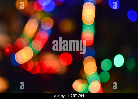 Christmas lights background. Blurred electric garland on Christmas tree. Red, green, yellow, orange, blue glow in - Stock Photo