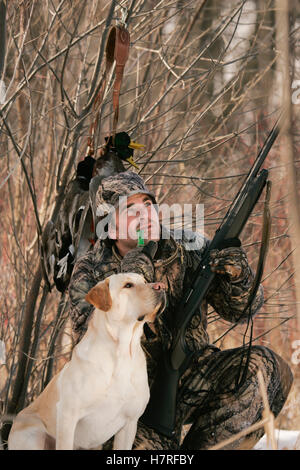 Duck Hunter With Yellow Lab holding a shotgun - Stock Photo