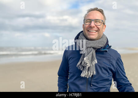 Happy laughing middle-aged man wearing glasses and a knitted woollen scarf standing on a deserted autumn beach on - Stock Photo