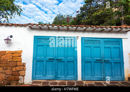 Blue garage doors on a white colonial building in Barichara, Colombia - Stock Photo
