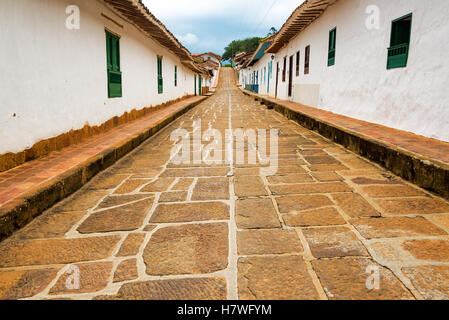 View of a beautiful street lined with historic colonial buildings in Barichara, Colombia - Stock Photo