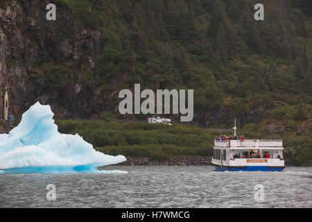 The M/V Ptarmigan tour boat stops to let visitors view a large iceberg in Portage Lake, Southcentral Alaska, USA - Stock Photo