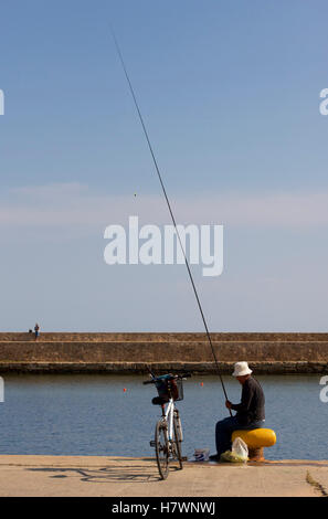 Man fishing on the sea wall in Venetian Harbour, Old Town, Chania, - Stock Photo