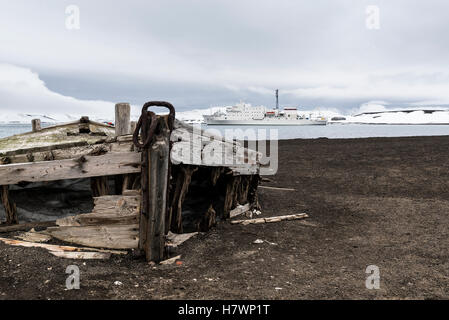 Old wooden boat abandoned on the shore at a whaling station with a cruise ship out in the water; Deception Island, - Stock Photo