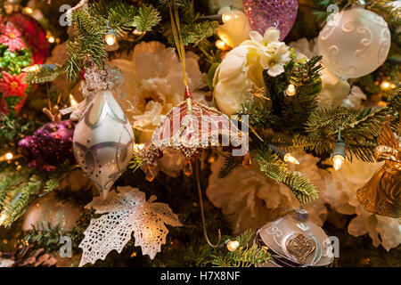 New Year toys. Close up of the toy in form of umbrella against decorative New Year tree. - Stock Photo