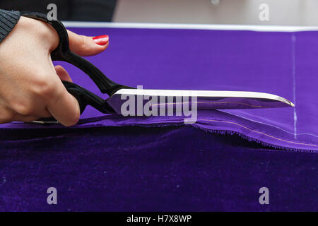 Scissors and violet textile. Close up photo if the female hand with the scissors cutting the violet fabric. - Stock Photo