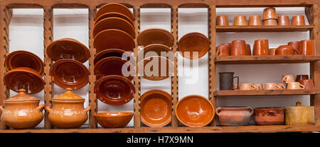 Clay dishes. Set of the clay dishes, plates, cups and saucepans on the wooden shelves. - Stock Photo