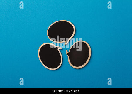 Top view of round chalk board speech bubbles on blue background, metaphor concept for communication - Stock Photo