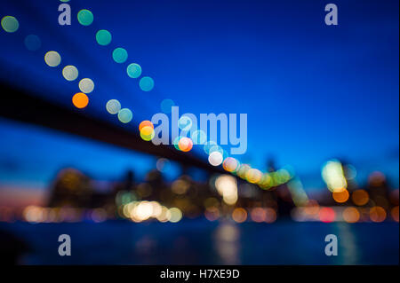Defocus scenic sunset view of the New York City skyline with Brooklyn Bridge and Downtown Manhattan from across - Stock Photo