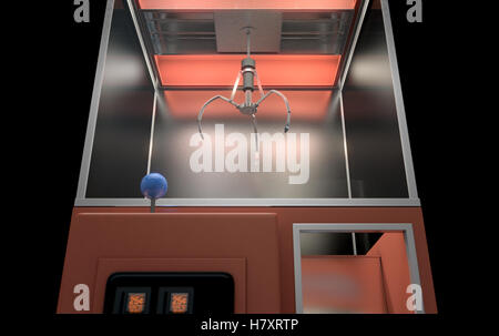 A 3D render of an empty arcade type claw grabber game on an isolated black background - Stock Photo