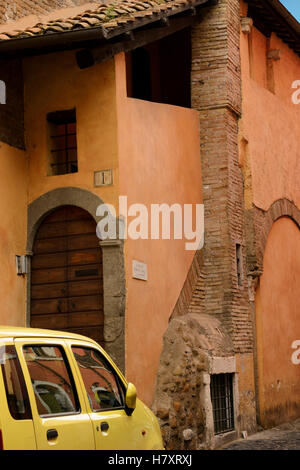 The small yellow car at an entrance of the terracotta house in the Trastevere area, Rome - Stock Photo