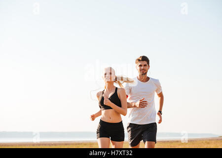 Smiling sports couple running together outdoors - Stock Photo