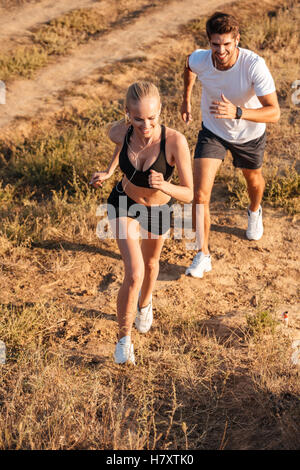 Athletic female runner and male fitness model running together outdoors - Stock Photo