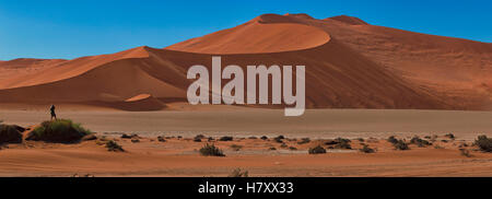 Man photographing the red sand dunes of Sossusvlei; Namibia - Stock Photo