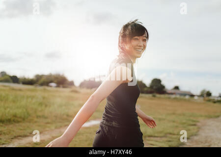 Outdoor shot of smiling young woman runner looking at camera. Chinese female walking on field in morning. - Stock Photo