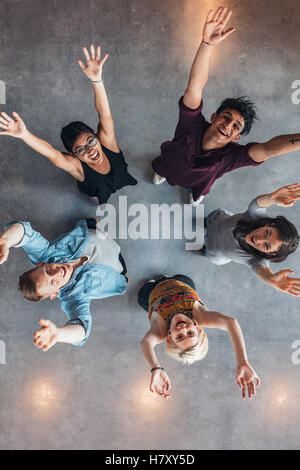 Overhead view of young people standing together looking up at camera with their arms raised. University students - Stock Photo